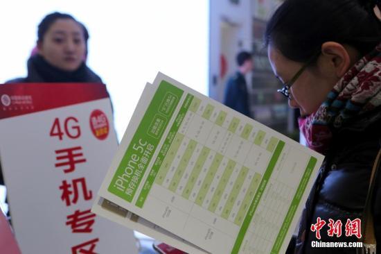 1月17日,北京金融街移动营业厅内,顾客正在体验4G手机。当天,中国移动与苹果公司正式面向中国大陆地区发售中国移动版iPhone5s及iPhone5c。中新社发 李慧思 摄