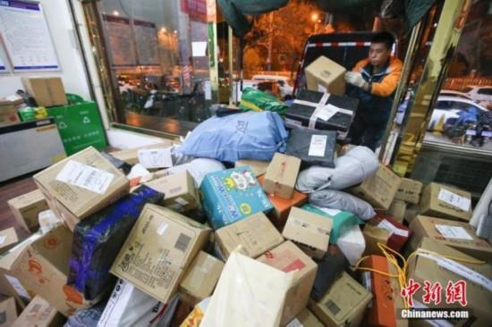 11月13日,山西太原的物流業工作人員加緊給快遞卸車。中新社記者 張云 攝